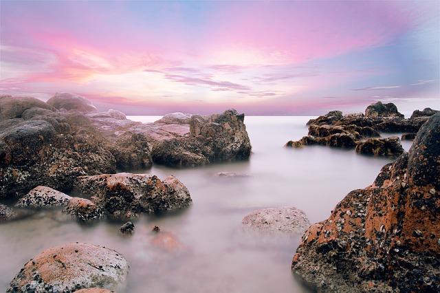 Východ slnka nad zálivom v mori s veľkými skalami