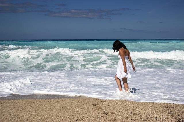 Opálená žena v bielych šatách stojí na kraji mora