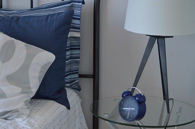 Posteľ s modrými vankúšmi, vedľa ktorej je sklenený stolík s budíkom.jpg
