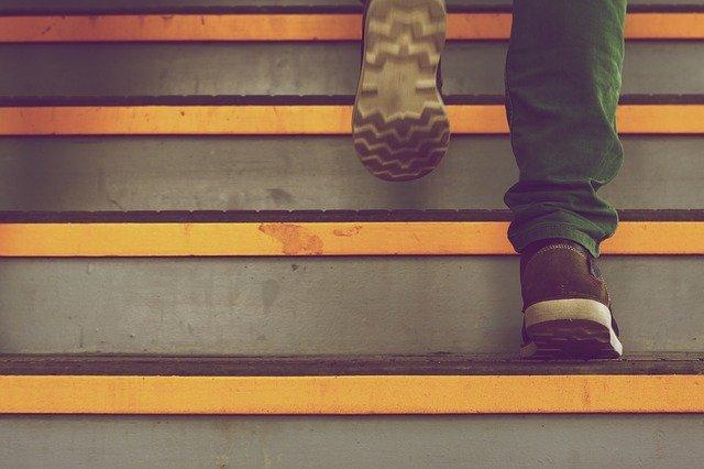 Človek v botaskách ide po schodoch.jpg